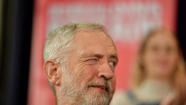 Le leader du Parti travailliste Jeremy Corbyn fait un clin d'oeil à un collègue lors d'un meeting politique à Hastings le 17 janvier 2019 [Ben STANSALL / AFP]