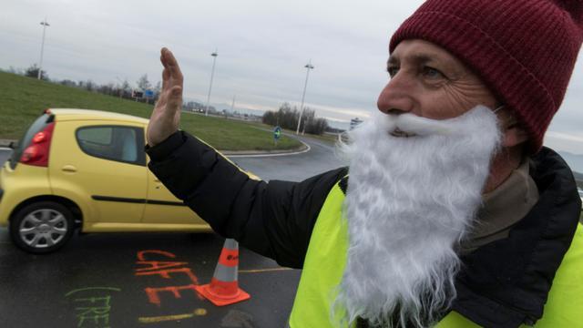 """Un """"gilet jaune"""" à un rond-point à Saint-Beauzire (centre), salue les automobilistes, le 15 décembre 2018 [Thierry Zoccolan / AFP]"""