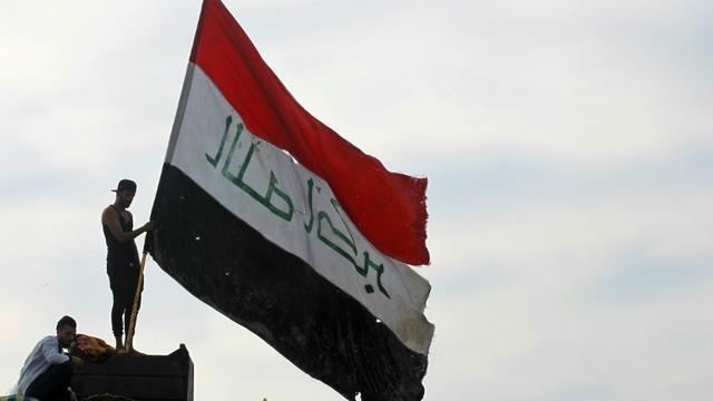 Un manifestant brandit le drapeau irakien dans la capitale Bagdad le 6 novembre 2019 [AHMAD AL-RUBAYE / AFP]