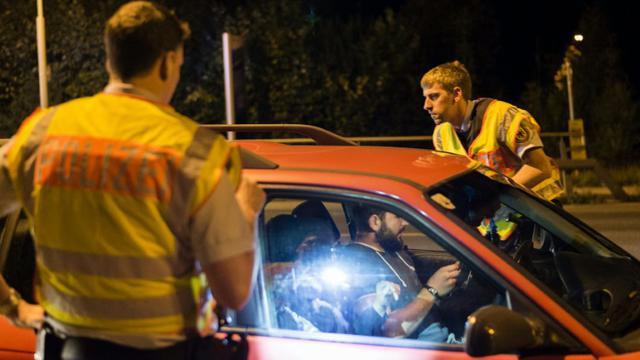 Un véhicule contrôlé par des policiers allemands le 13 septembre 2015 à Freilassing à la frontière de l'Allemagne et de l'Autriche [GUENTER SCHIFFMANN / AFP]