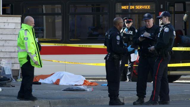 Des policiers près d'un corps caché par un drap, le 23 avril 2018 à Toronto, au Canada, après qu'un homme au volant d'une camionnette a fauché une dizaine de piétons  [Lars Hagberg / AFP]