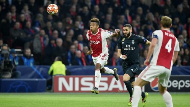 Le Français du Real Madrid Karim Benzema (c) entre deux joueurs de l'Ajax dont David Neres (g), en 8e de finale aller de la C1, le 13 février 2019 à Amsterdam  [JOHN THYS          / AFP]