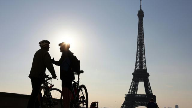 """Deux cyclistes discutent devant la tour Eiffel avant de participer à la """"journée sans voiture"""" organisée par la mairie de Paris, le 27 septembre 2015 [LUDOVIC MARIN / AFP/Archives]"""
