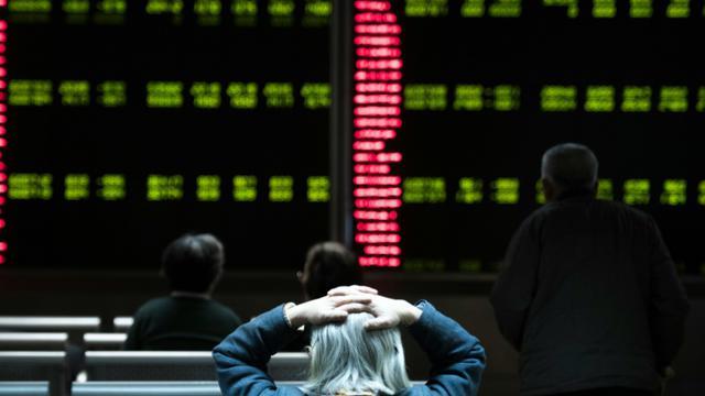 Des investisseurs regardent des écrans de cotation dans une société de Bourse à Pékin le 7 janvier 2016 [FRED DUFOUR / AFP]