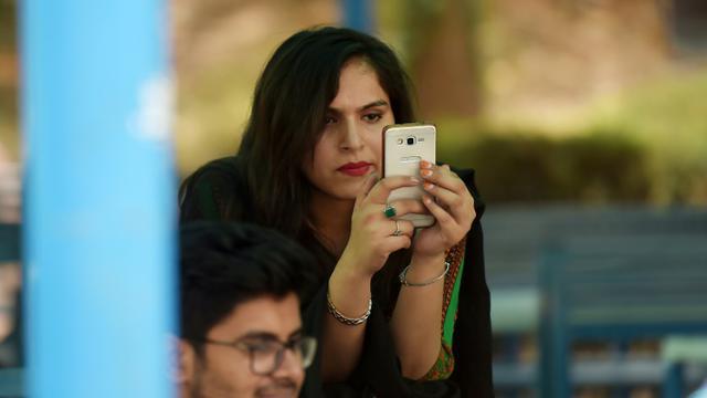 Une étudiante utilise un smartphone sur le campus d'Islamabad le 12 juillet 2018 [Aamir QURESHI / AFP]