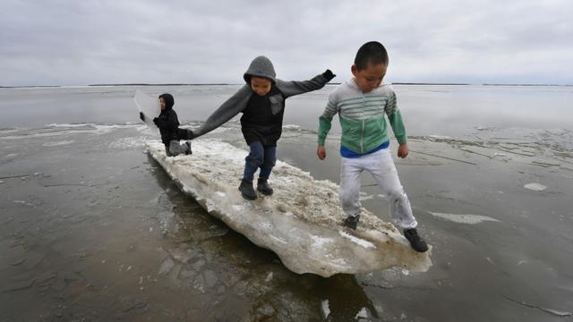 Des enfants jouent sur un bloc de glace en train de fondre dans le village eskimo yupik de Napakiak, le 18 avril 2019 en Alaska [Mark RALSTON / AFP]