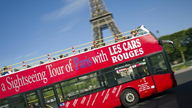 Un bus de la compagnie des Cars rouges passe devant la Tour Effeil à Paris, le 3 août 2012 [Lionel Bonaventure / AFP/Archives]