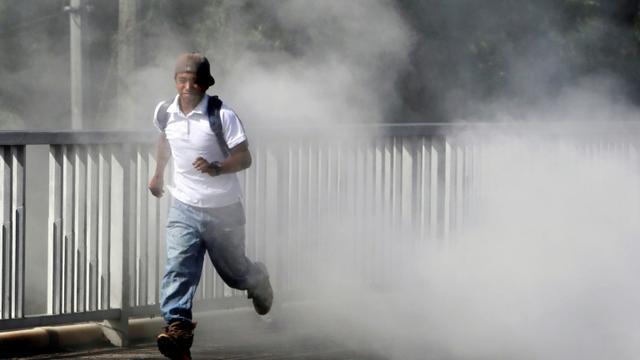 Un homme court pour échapper à la fumée de pneus en train de brûler le 12 juin 2018 à Sebaco, Nicaragua [Inti Ocon / AFP]