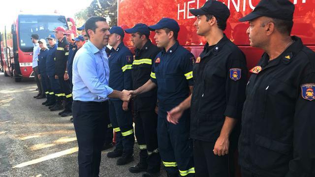 Le Premier ministre grec Alexis Tsipras (c) salue les pompiers ayant combattu les incendies meurtriers de Mati, à l'est d'Athènes, le 30 juillet 2018 [- / GREEK PRIME MINISTER'S PRESS OFFICE/AFP/Archives]