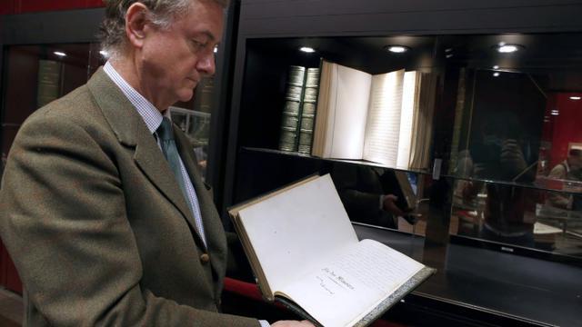 Un commissaire-priseur présente le manuscrit des Mémoires d'outre-tombe de Chateaubriand, le 25 novembre 2013 à l'Hôtel Drouot à Paris [Thomas Samson / AFP]