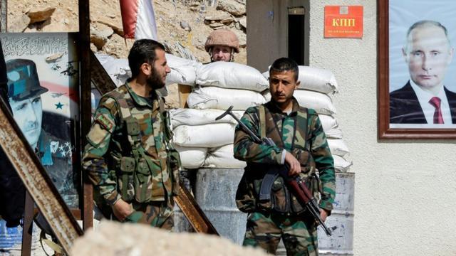 Des forces progouvernementales syriennes devant des portraits des présidents russe et syrien, Vladimir Poutine et Bachar al-Assad, au passage d'Al-Wafidine à la limite de la Ghouta orientale, le 1er mars 2018 [LOUAI BESHARA / AFP]