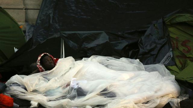 Un migrant dans un campement de fortune installé devant la mairie du 18e arrondissement le 16 septembre 2015 à Paris [FLORIAN DAVID / AFP]