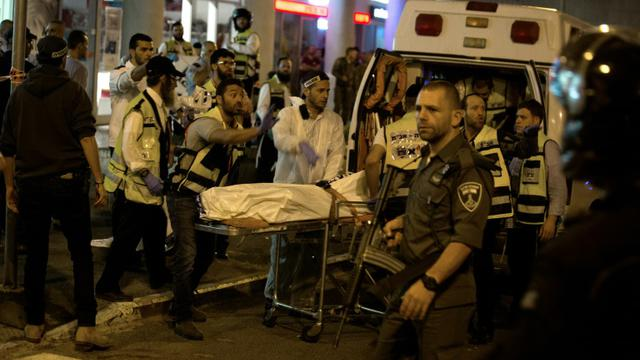 Des ambulanciers transportent le corps d'un Israélien, le 21 octobre 2015 à Jérusalem [MENAHEM KAHANA / AFP]