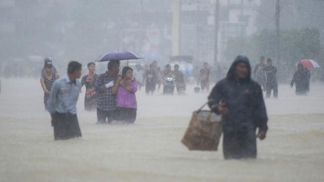 Des habitants de la ville de Pégou en Birmanie dans les rues inondées de leur ville, le 29 juillet 2018 [Ye Aung THU / AFP]
