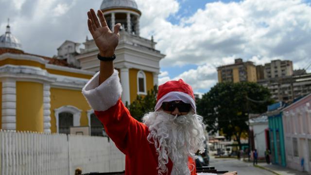 """Un homme déguisé en Père Noël lors de l'opération """"Santa en las calles"""" (le Père Noël dans la rue), le 16 décembre 2017 à Caracas, au Venezuela [FEDERICO PARRA / AFP]"""