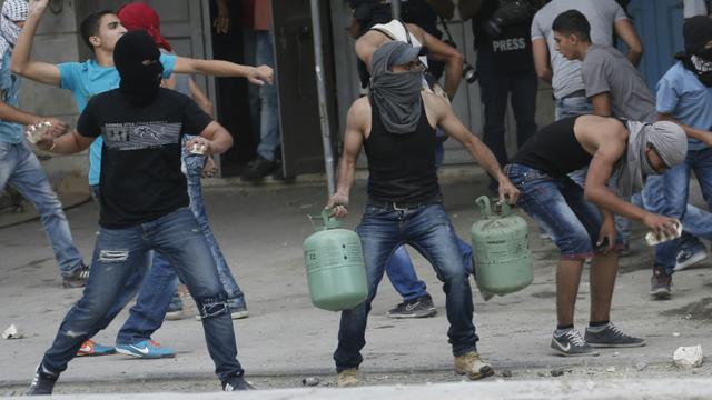 De jeunes palestiniens lancent des pierres contre les forces de sécurité israéliennes au checkpoint de Qalandia entre Jérusalem et Ramallah, le 6 octobre 2015 [ABBAS MOMANI / AFP]