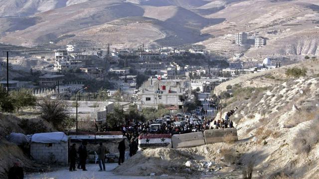 Photo fournie par l'agence officielle syrienne Sana le 11 janvier 2017 montrant des habitants des villages de la région rebelle de Wadi Barada qui attendent de pouvoir quitter la zone [ / SANA/AFP]