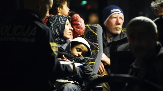 Des policiers solvènes enregistrent les migrants à  bord d'un bus le 21 octobre 2015 à Brezice en Solvénie [- / AFP]