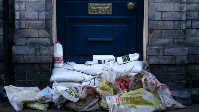 Des bouteilles de lait sont déposées au dessus de sacs de sable pour protéger l'entrée d'une maison des innondations à York, au nord de l'Angleterre, le 29 décembre 2015  [JUSTIN TALLIS / AFP]