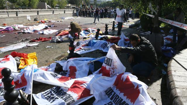 Des corps sans vie recouverts de bannières jonchent le sol le 10 octobre 2015 à Ankara après des attentats meurtriers [ADEM ALTAN / AFP]