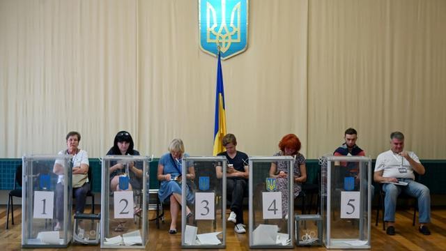 Des observateurs installés près des urnes dans un bureau de vote, lors des législatives, le 21 juillet 2019 à Kiev, en Urkaine [Sergei Supinsky / AFP]