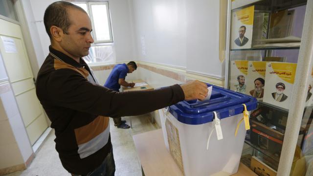Un Iranien dépose son bulletin dans l'urne le 29 avril 2016 à Robat Karim [ATTA KENARE / AFP]