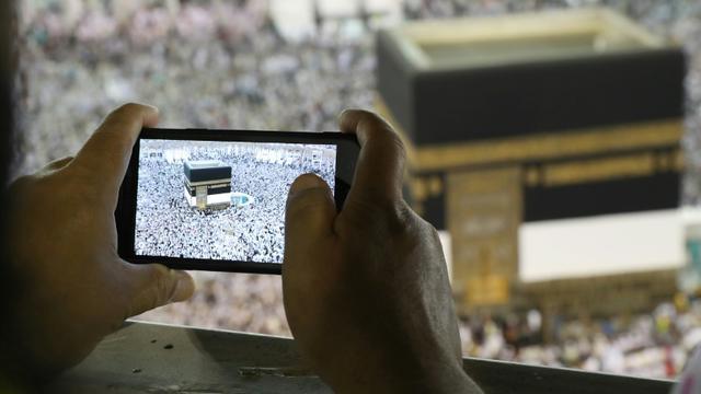 Un homme prend une photo de la Kaaba, au centre de la Grande mosquée de La Mecque le 15 août 2018 à l'occasion du grand pèlerinage [Bandar Al-DANDANI / AFP]