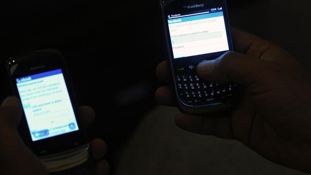 Des Pakistanais consultent le site internet de Facebook sur leur téléphone portable [Aamir Qureshi / AFP/Archives]