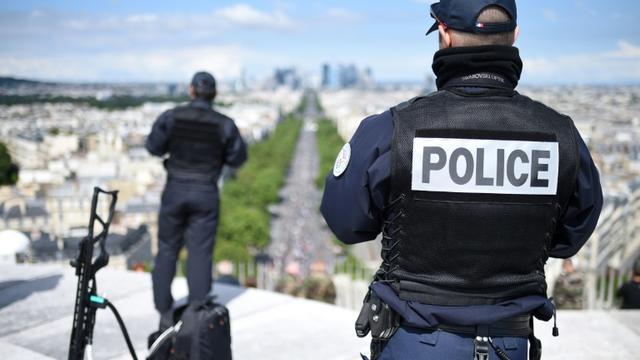Des policiers suveillent le défilé militaire depuis le sommet de l'Arc de Triomphe, le 14 juillet 2016 à Paris [STEPHANE DE SAKUTIN / AFP/Archives]