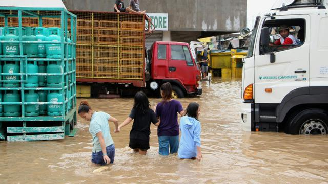 Des habitants de la ville de Baao marchent les rues inondées après le passage de la tempête Usman, le 30 décembre 2018 [Simvale SAYAT / AFP]