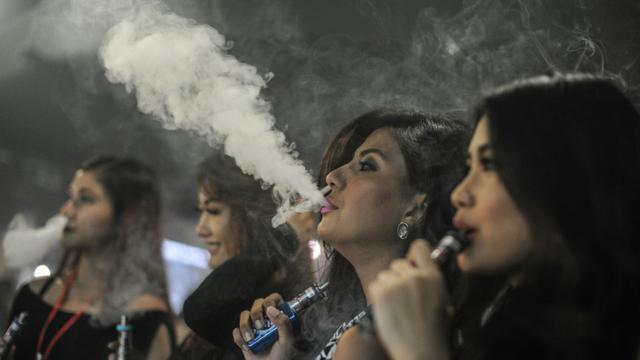 Des personnes fument des cigarettes électroniques pendant la VapeFair à Kuala Lumpur, le 5 décembre 2015 [MOHD RASFAN / AFP/Archives]