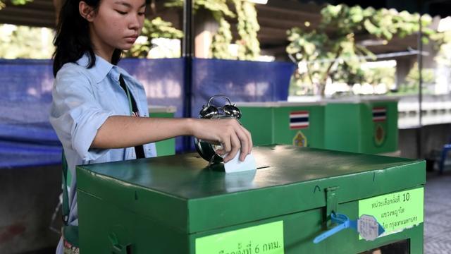Une Thaïlandaise dépose son bulletin de vote dans une urne à Bangkok le 24 mars 2019 [Lillian SUWANRUMPHA                 / AFP]