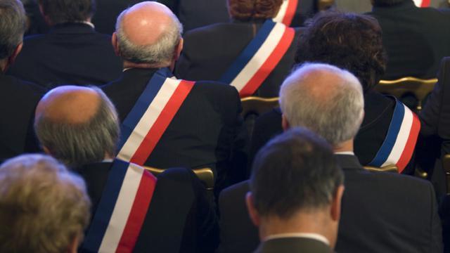 Des maires ayant revêtu leur écharpe tricolore écoutent Nicolas Sarkozy (hors champ), alors président de la République, le 20 novembre 2009 u palais de l'Elysée à Paris [Charles Platiau / POOL/AFP/Archives]