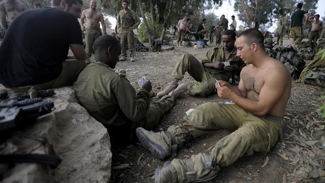 Des soldats israéliens jouent aux cartes à la frontière d'Israël avec le bande de Gaza, le 5 août 2014, après le retrait des troupes israéliennes de ce territoire palestinien [David Buimovitch / AFP]