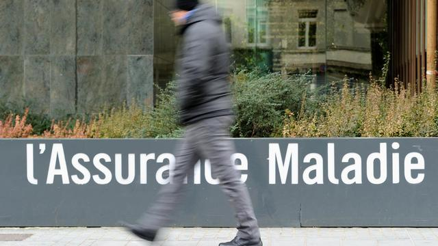 Un homme passe devant un bâtiment de l'Assurance maladie, le 29 janvier 2014 à Lille [Philippe Huguen / AFP/Archives]
