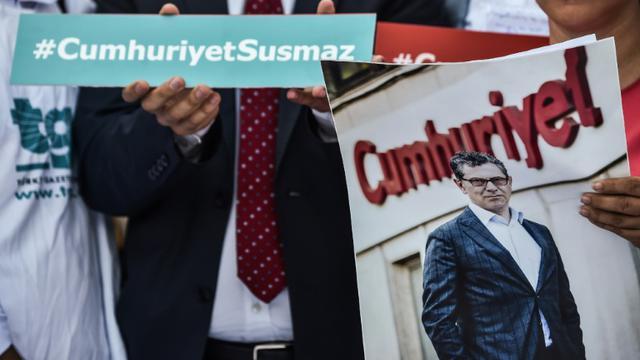 Un manifestant bandit le portrait du journaliste Kadri Gürsel le 24 juillet 2017 lors d'une manifestation devant le palais de justice d'Istanbul [OZAN KOSE / AFP/Archives]