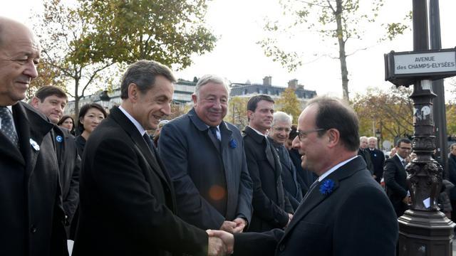 Poignée de mains entre François Hollande (D) et Nicolas Sarkozy, en présence de Jean-Yves Le Drian, Gérard Larcher, Manuel Valls et Claude Bartolone lors de la commémoration de l'amistrice, le 11 novembre 2015 sur les Champs Elysées à Paris [ERIC FEFERBERG / POOL/AFP]