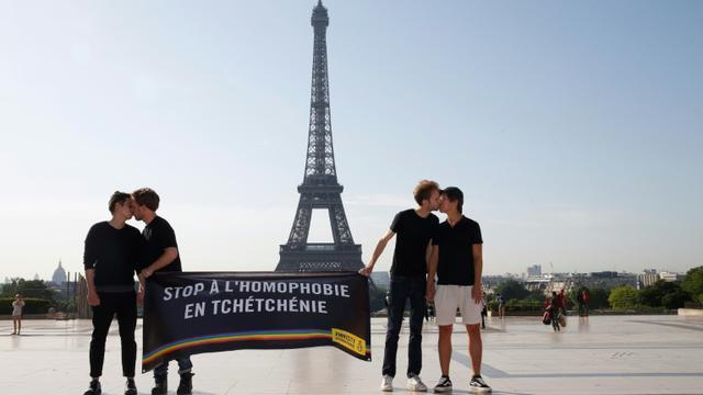 Des militants d'Amnesty s'embrassent devant la tour Eiffel à Paris dans le cadre d'une manifestation contre l'homophobie en Tchétchénie, le 29 mai 2017 [GEOFFROY VAN DER HASSELT / AFP]
