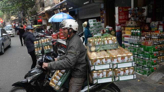 Un livreur quitte un magasin de boissons avec des canettes de bière au centre-ville de Hanoi le 23 janvier 2017, alors que les Vietnamiens se préparent à célébrer le Nouvel An lunaire.