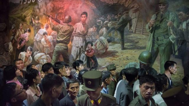 Un groupe de visiteurs passe devant un tableau représentant des soldats américains s'apprêtant à tuer des civils nords-coréens, le 24 juillet 2017 au Musée des atrocités de guerre américaines à Sinchon, en Corée du Nord [Ed JONES / AFP]