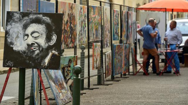 Des vendeurs de peinture ambulants dans les rues de Marciac, le 31 juillet 2018, pendant la 41e édition de Jazz in Marciac [REMY GABALDA / AFP]