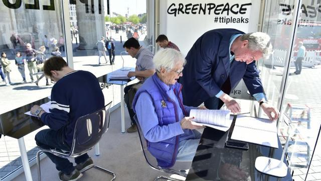 Le député des Verts allemand Hans-Christian Stroebele (C) lit des documents sur les négociations du TTIP révélés par Greenpeace, à Berlin le 2 mai 2016 [John MACDOUGALL / AFP]
