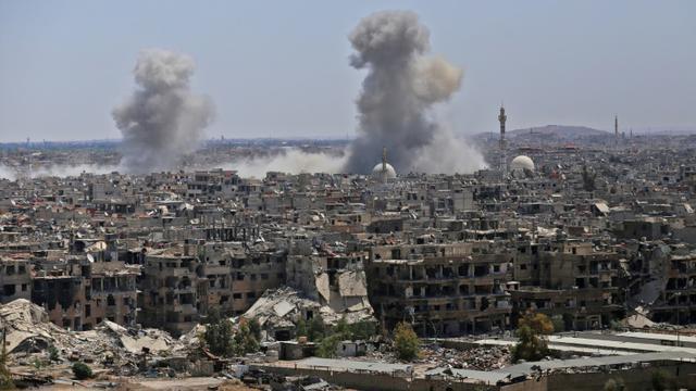 Photo prise le 24 avril 2018 lors d'un voyage de presse organisé par le gouvernement montrant de la fumée s'élevant de bâtiments dans le camp de réfugiés palestiniens de Yarmouk, près de Damas, lors de bombardements visant le groupe Etat islamique (EI) [Maher AL MOUNES / AFP]