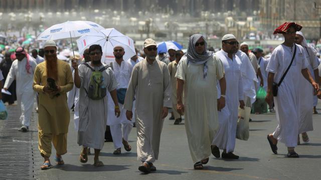 Des pèlerins musulmans marchent dans une rue de la ville sainte de la Mecque en Arabie saoudite avant le début du hajj annuel, le 18 août 2017 [AHMAD AL-RUBAYE / AFP]