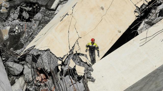 Les services de secours italiens fouillent les décombres du viaduc effondré à Gênes, le 14 août 2018 [Valery HACHE / AFP]