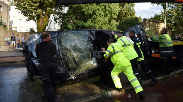 Des secours aident à renverser une Ford Fiesta dans laquelle deux personnes sont mortes le 23 août 2015 [Pascal Guyot / AFP]