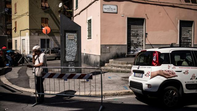 """Un homme dans la rue Fillak, près de la """"zone rouge"""", située sous ce qui reste du pont Morandi à Gênes (Ligurie), le 13 septembre 2018 [MARCO BERTORELLO / AFP]"""