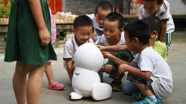 Des enfants de l'école maternelle Yiswind en Chine autour du robot Keeko, le 30 juillet 2018 [GREG BAKER / AFP]