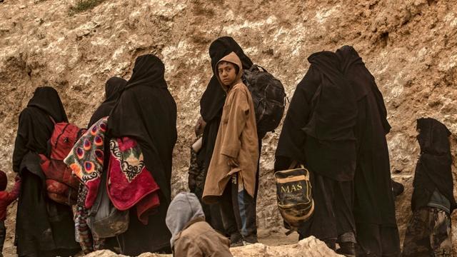 Des membres présumés du groupe Etat islamique (EI) fuient le village de Baghouz (Syrie), le 14 mars 2019 [Delil souleiman / AFP]