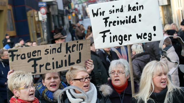 """Des femmes manifestent avec des pancartes disant """"Nous ne sommes pas du gibier. Bas les pattes !"""" à Hambourg le 10 janvier 2016 [Bodo Marks / dpa/AFP]"""